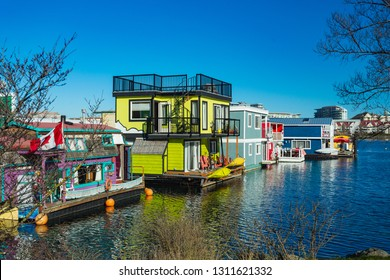 Floating Home Village colorful Houseboats Water Taxi Fisherman's Wharf Reflection Inner Harbor, Victoria British Columbia Canada Pacific Northwest. Area has floating homes, piers, restaurants.