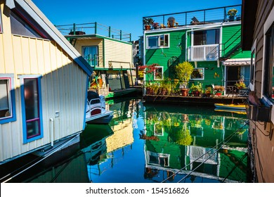 Floating Home Village Green Brown Houseboats Fisherman's Wharf Reflection Inner Harbor, Victoria British Columbia Canada Pacific Northwest.  Area has floating homes, boats, piers, and restaurants.