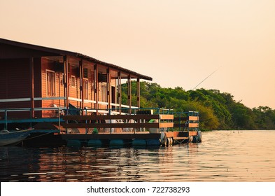 Floating house on the banks of a river in Pantanal, Brazil. Peaceful fisherman place with the floating house and a boat, nobody around at a wonderful sunset.