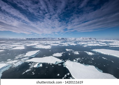 floating ice in the arctic ocean with pretty clouds above blue sky