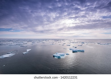 floating ice in the arctic ocean with pretty clouds above and blue sky