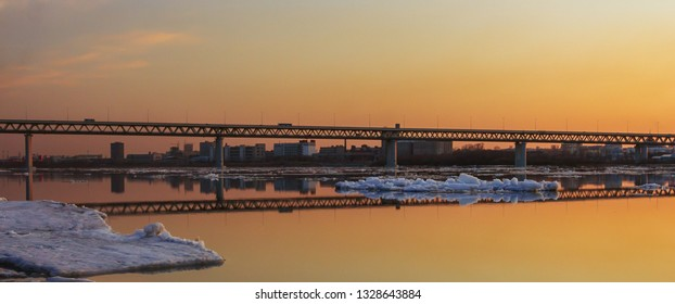 Floating of ice on the Oka River and the bridge in the evening at sunset