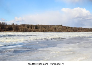 Floating ice/drifting floes on the frozen river Daugava, Latvia. Early spring floods concept. Landscape view on the shore of the river.