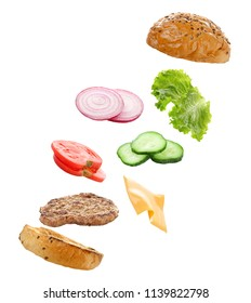 Floating ingredients for delicious burger on white background