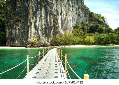 Floating plastic pier connected to white sand beach with white cliff and blue sky