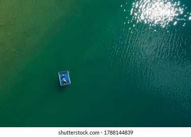 Floating platform with a sun tanning couple aerial top view. Bright sn reflecting in green lake waves. Peruca Lake, Dalmatia, Croatia