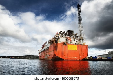 Floating, production, storage and offloading FPSO vessel moored to the shore in a port, close-up. Riga, Latvia. Fuel and power generation, industry, global communications, environmental damage