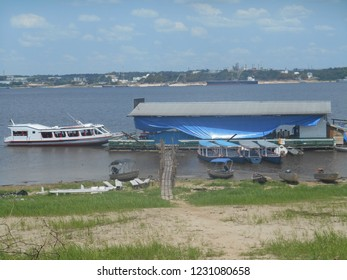 Floating restaurant next to the island located in Rio Negro, Brazil, with boats nearby