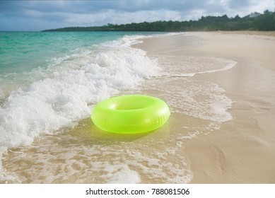 floating ring on sandy beach with waves reflecting in the summer sun