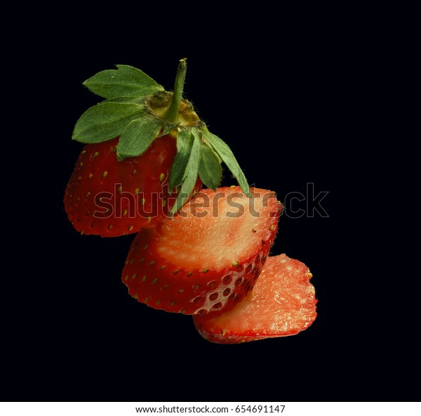 Floating sliced strawberry on isolated solid black background