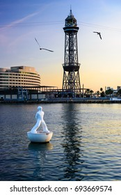 Floating statue in the port of Barcelona, with seagulls, the World Trade Center and the tower of the cable way on the background at sunset. 10/24/2014