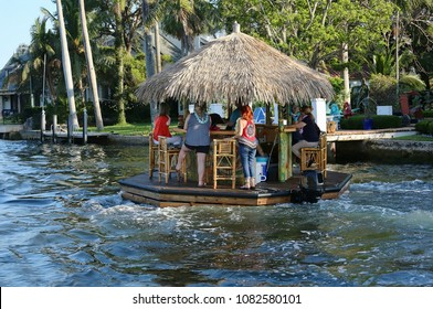 Floating tiki bar cruises down the Intracoastal Waterway in Fort Lauderdale, Florida, USA.
