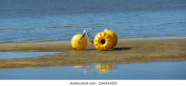 Floating water tricycle rests at low tide on Biloxi Beach.