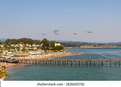 A flock of pelicans fly over the beach at Capitola.