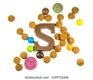 Flock of Pepernoten strooigoed with chocolate letter S, top view on white background for annual Sinterklaas holiday event in the Netherlands on december 5th
