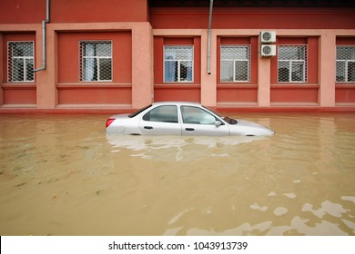 Flood in the city. Car half in the water on street.