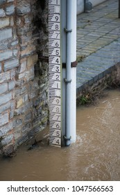 flood leve guage measuring rain fall surrounded by brown river water