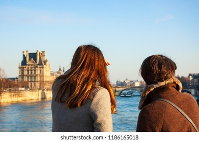 Flood in Paris, France. Women (back view) admiring view of Louvre museum  with raising water in Seine river.