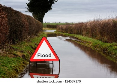 Flood warning sign on a flooded country road showing adverse driving conditions