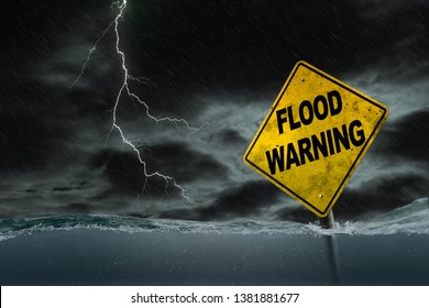 Flood Warning sign submerged in rising water against a stormy background with rain and lightning. Dirty and angled sign adds to the drama.