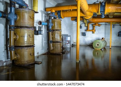 """Flooded abandoned fallout shelter. Ventilation room with yellow pipes and green filters. Translations: """"Аварийный выход""""-  Emergency exit """"Закрыто - closed"""" """"Открыто"""" - open """"Воздуха"""" - Of air"""