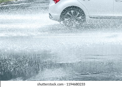 flooded asphalt city road during heavy rain. water spraying from car wheels in motion