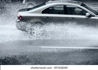 flooded city road with rain puddles and with riding cars splashing water from the wheels