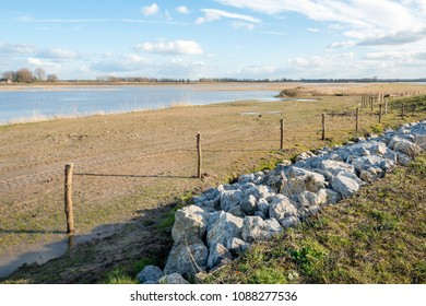 Flooded part of a Dutch polder with in front a fence of wooden poles and wire as well as rock chunks diagonally in the picture.