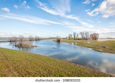 Flooded polder on a sunny day in the end of the winter season. In the background a farmer's barn with an orange tile roof was built on an elevation.