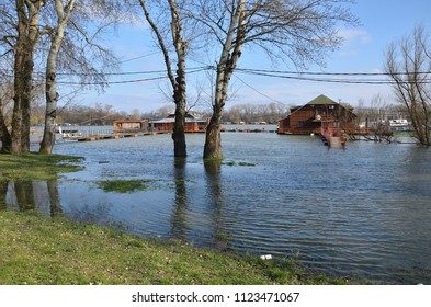 Flooded promenade along a river bank in a city area