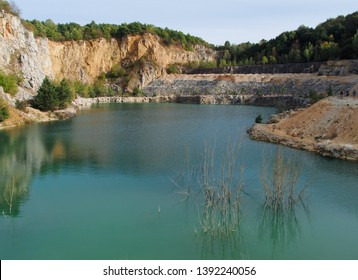 Flooded quarry in Europe. The stone quarry lake with crystal clean water great for diving. Abandoned quarry filled with water serves as a beautiful natural swimming pool.