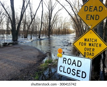 Flooded road with warning signs