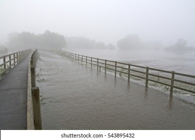 Flooded roadway in Lacock, Wiltshire on a misty July day with water running under the field fences.