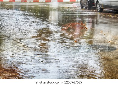 Flooding, winter rains in Israel. Rain Water floods the pavement and the cars road, raindrops and circles on the water