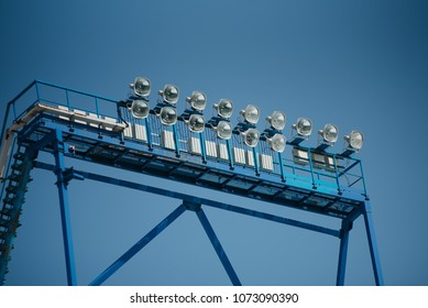 Floodlight mast with some lights on against dark blue sky. Stadium lights.