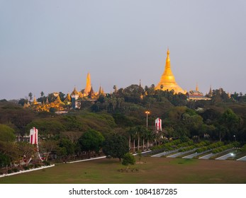 The floodlighted Shwedagon Pagoda in Yangon, Myanmar just after sunset with the People Park in the foreground.