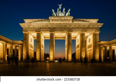 The floodlit Brandenburg Gate in Berlin with a few fleeting shadows of anonymous Berliner's - Symbol of Germany.