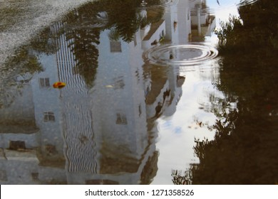 Floods in Israel. Big puddle, pouring rain, a reflection of a residential building in the water