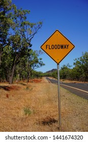 Floodway - warning sign in the Australian Outback. Surrounded by a dusty road and some green trees.