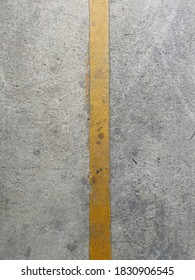 Yellow​ line​ on​ the​ cement​ floor.