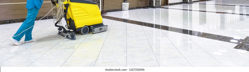 Floor care with washing machine in an office lobby. Panorama of cleaning service with vacuum equipment on shiny marble floor in the luxury interior of company. Concept of professional cleaning job.