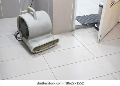 Floor dryer blower fan machine drying wet floor in public bathroom