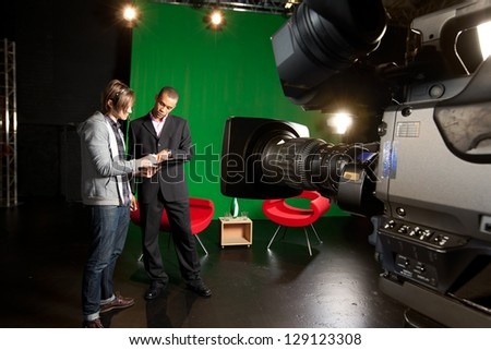 Floor manager and presenter planning a television broadcast with a studio camera in the foreground