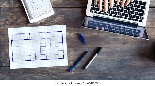 Floor plan drawing with architect designing home on computer, old wooden desk with blueprint of house or apartment project