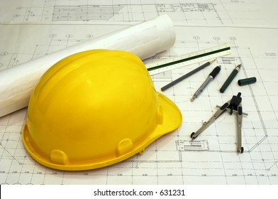 Floor plans and a hard hat with various drawing tools - scale ruler, compass, pen and pencil