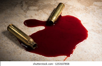 Floor with a pool of blood and AR-15 cartridges that have been shot