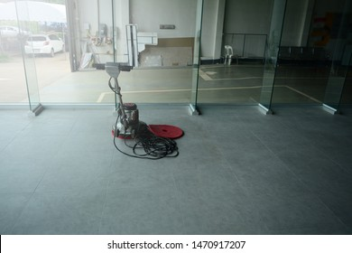 a floor scrubber machine put on the floor  in gk=lasses room while cleaning at the  buildings  and a  white service car parked at outside