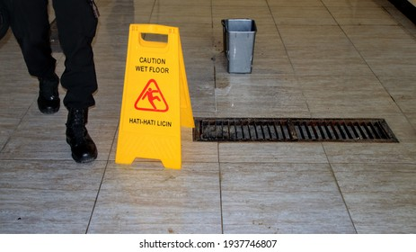 The floor is slippery after being mopped, marked with a sign Caution Wet Floor