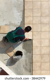 Floor tiles installation. Man installs ceramic tile