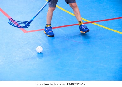 Floorball child boy player with stick and ball. Children playing florball sport